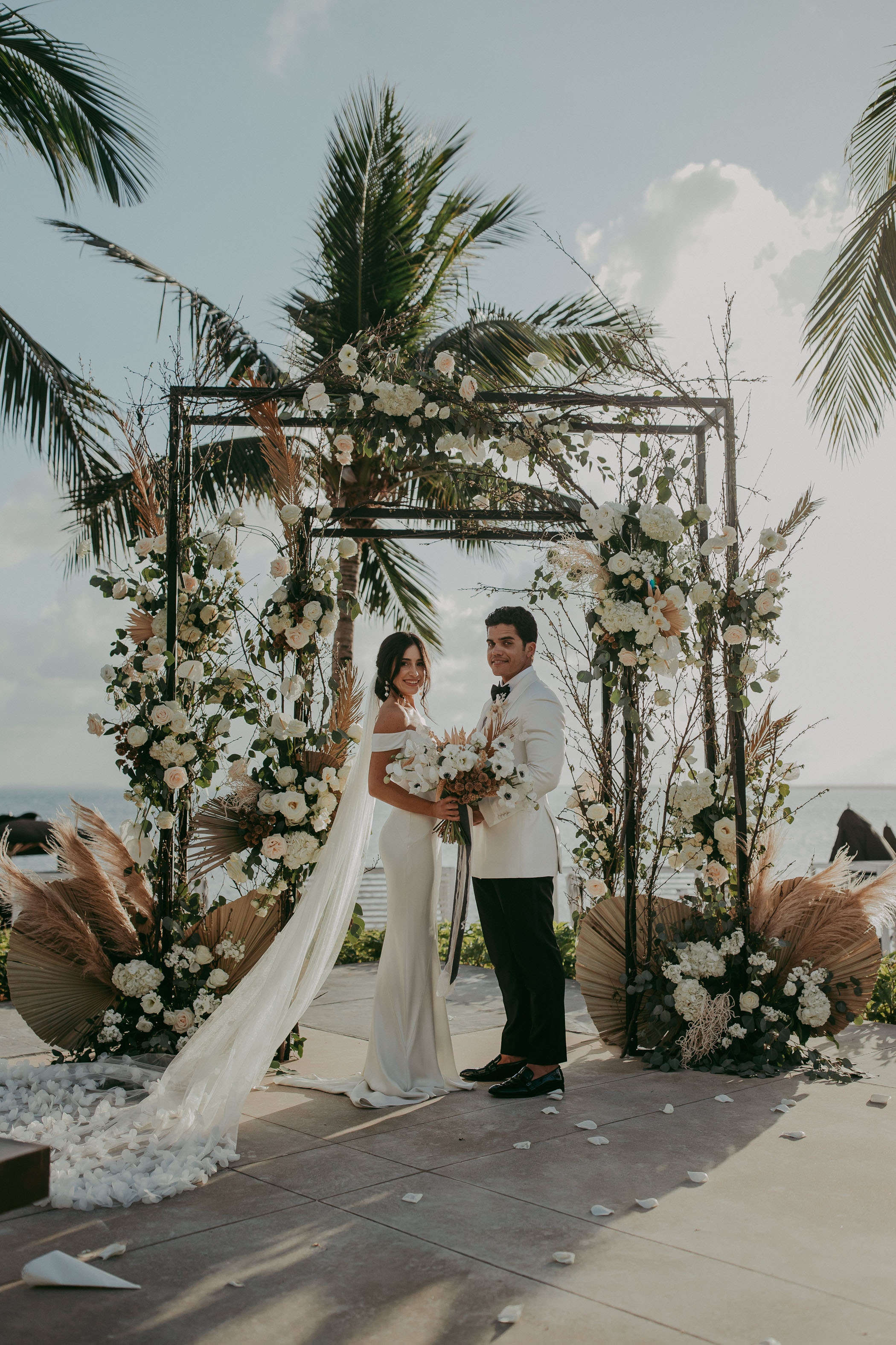 Bride and groom in front of their ceremony arch covered in white flowers