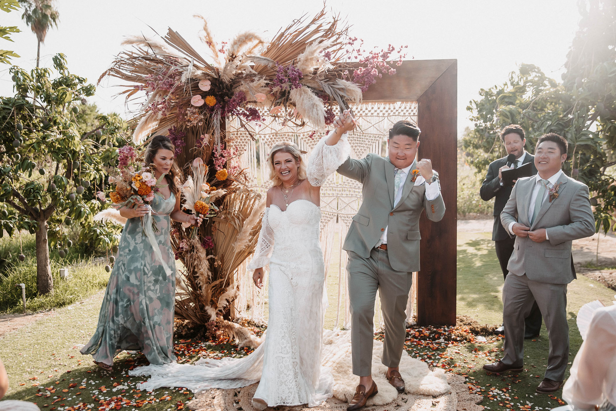 """A bride and groom after saying """"i do"""" in front of a macramé alter"""