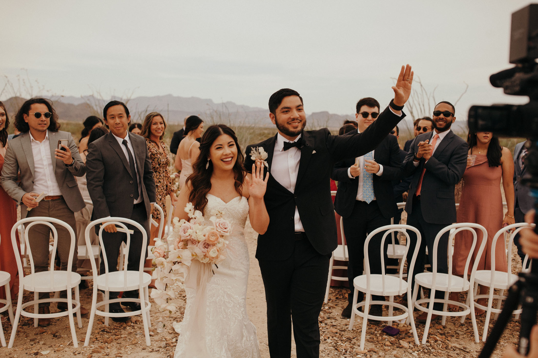 Happy couple waving to their friends after saying their vows