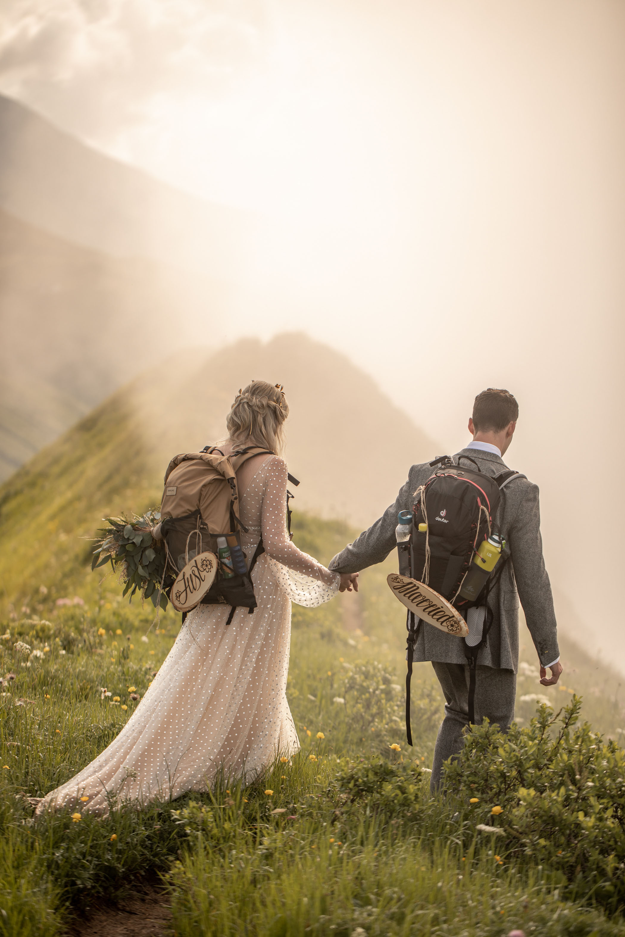 """bride and groom hiking with """"just married"""" signs on their backpacks"""