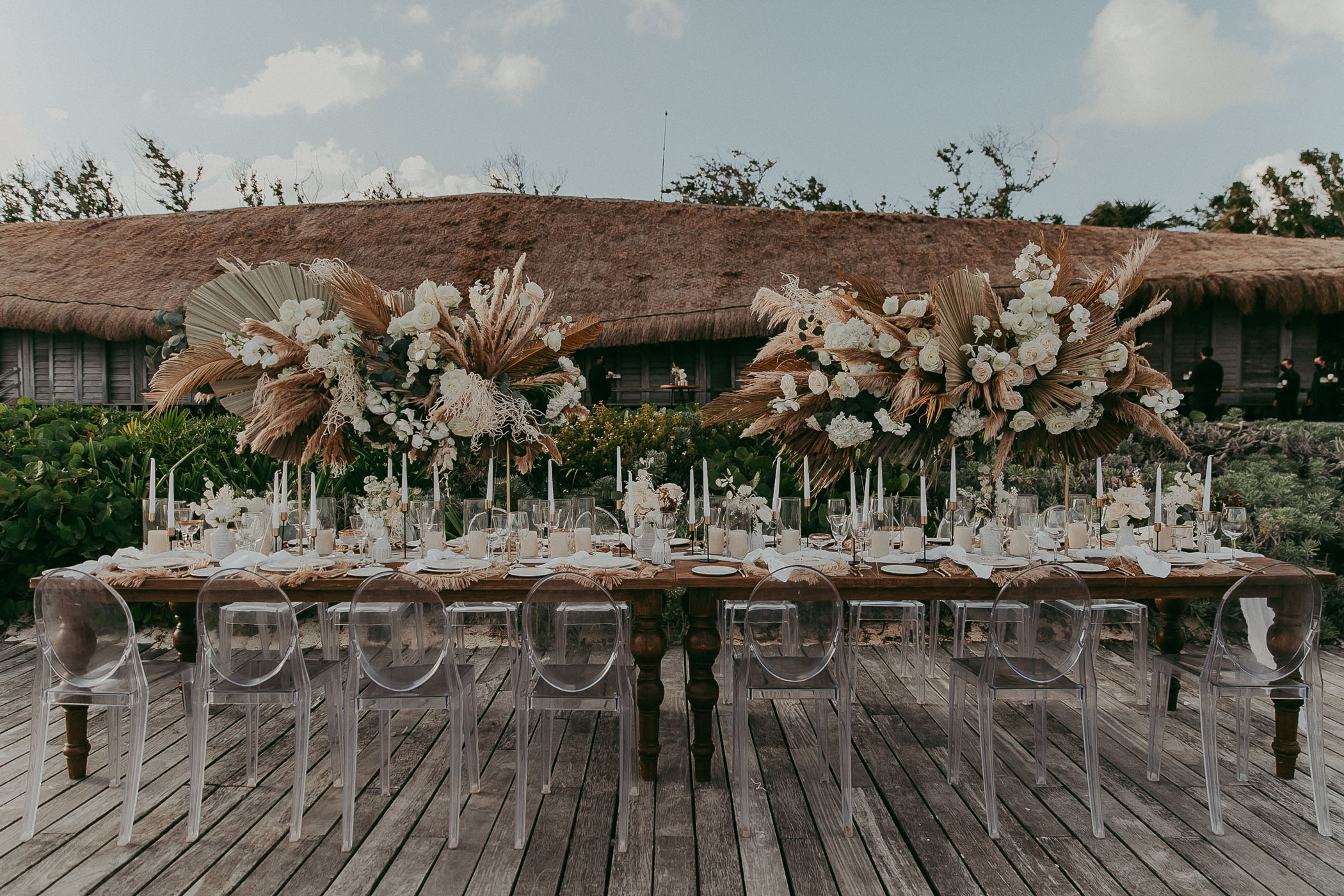 Pampas grass, ghost chair, and wooden wedding recption table