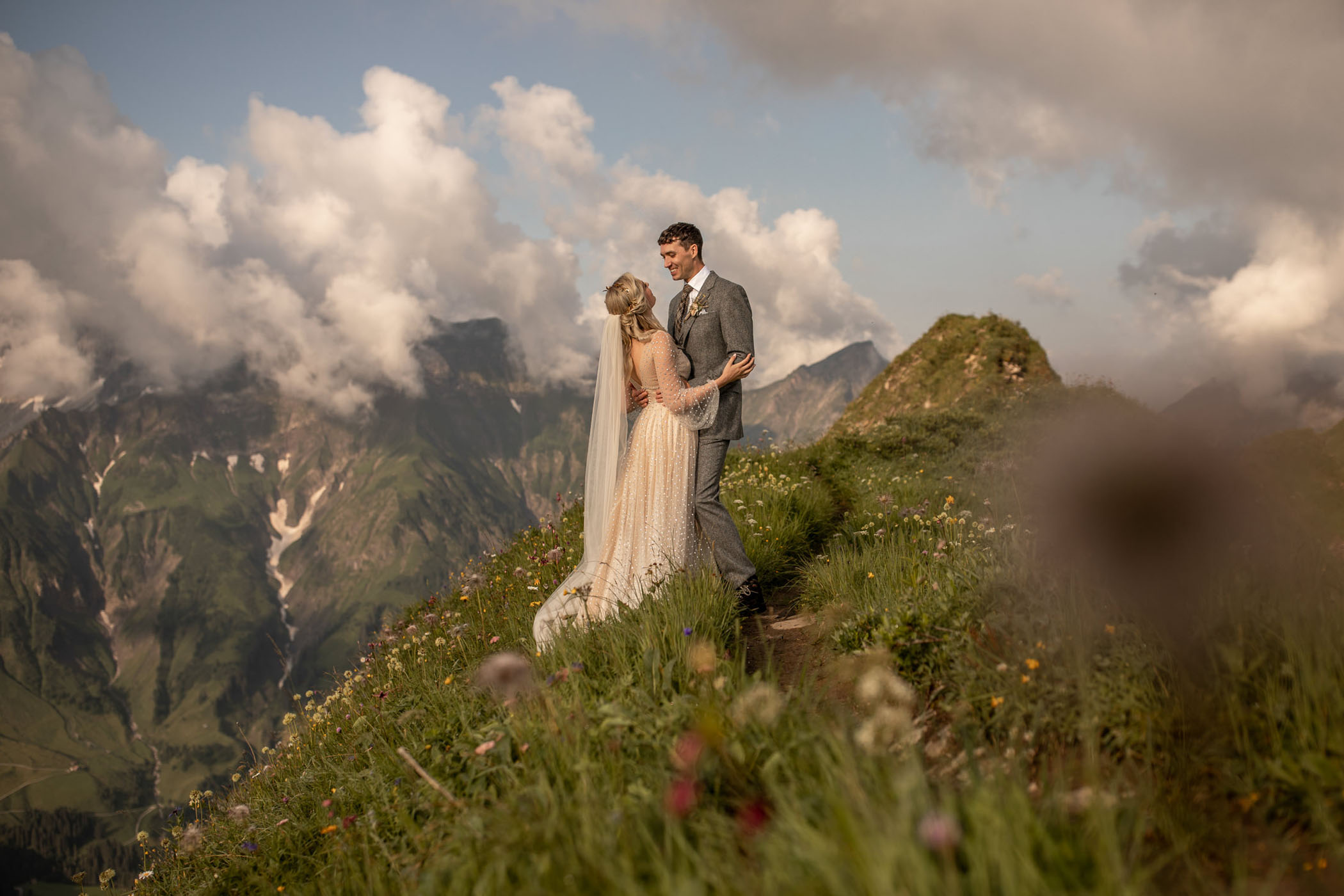 Fluffy clouds, mountain tops, and wildflowers surround a happy bride and groom