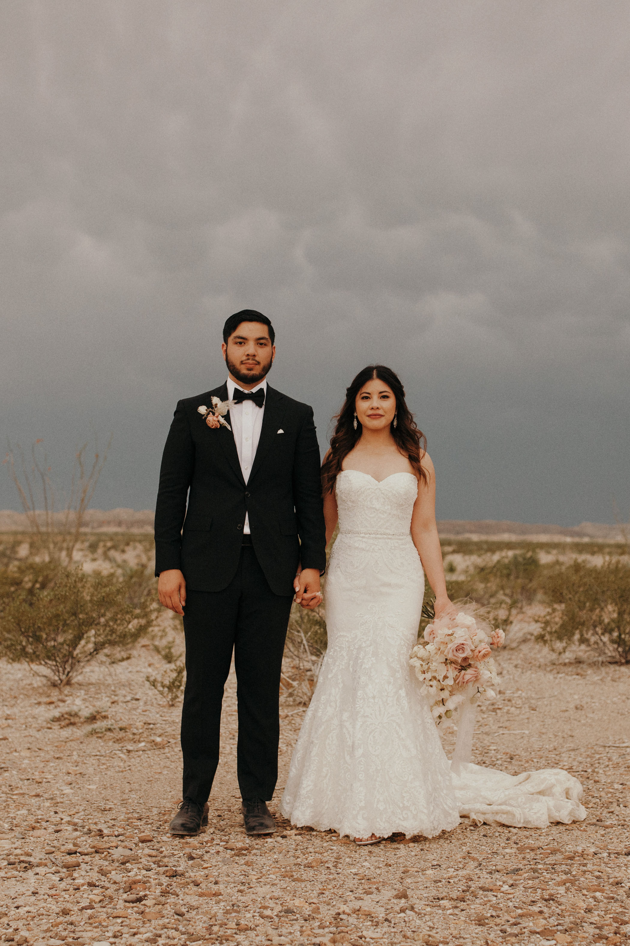 Bride and groom holding hands as a storm approaches