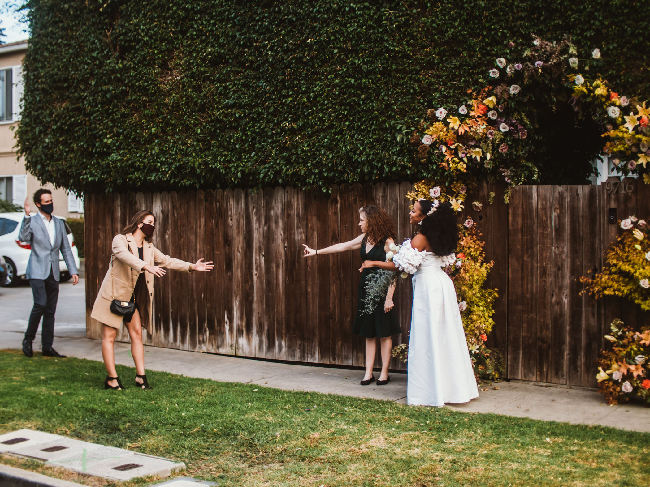 Masked wedding guests give a socially distant greeting