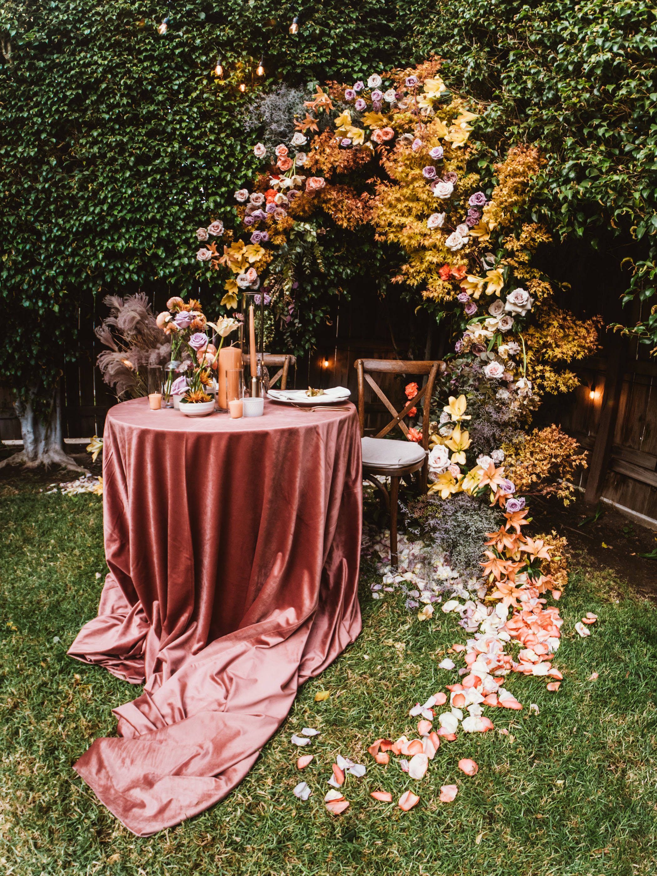 Colorful floral arch and pink wedding table cloth