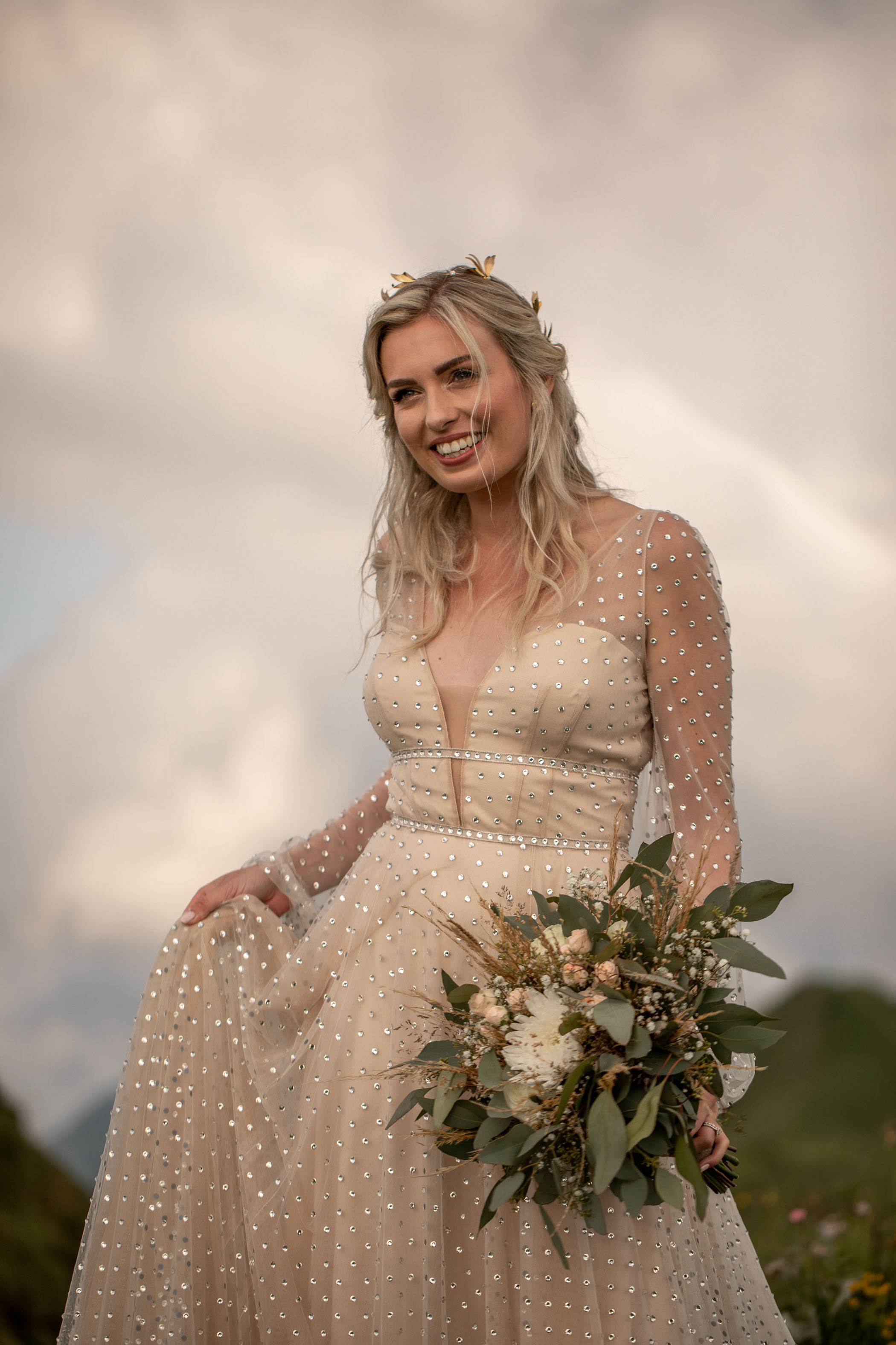 Bride in gold and rhinestone dress holding eucalyptus bouquet