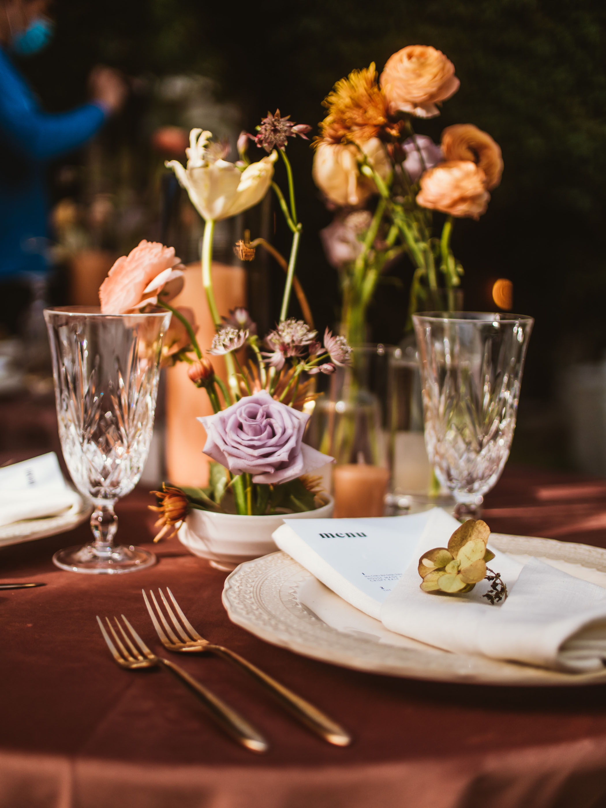 Wedding table setting with orange and purple flowers