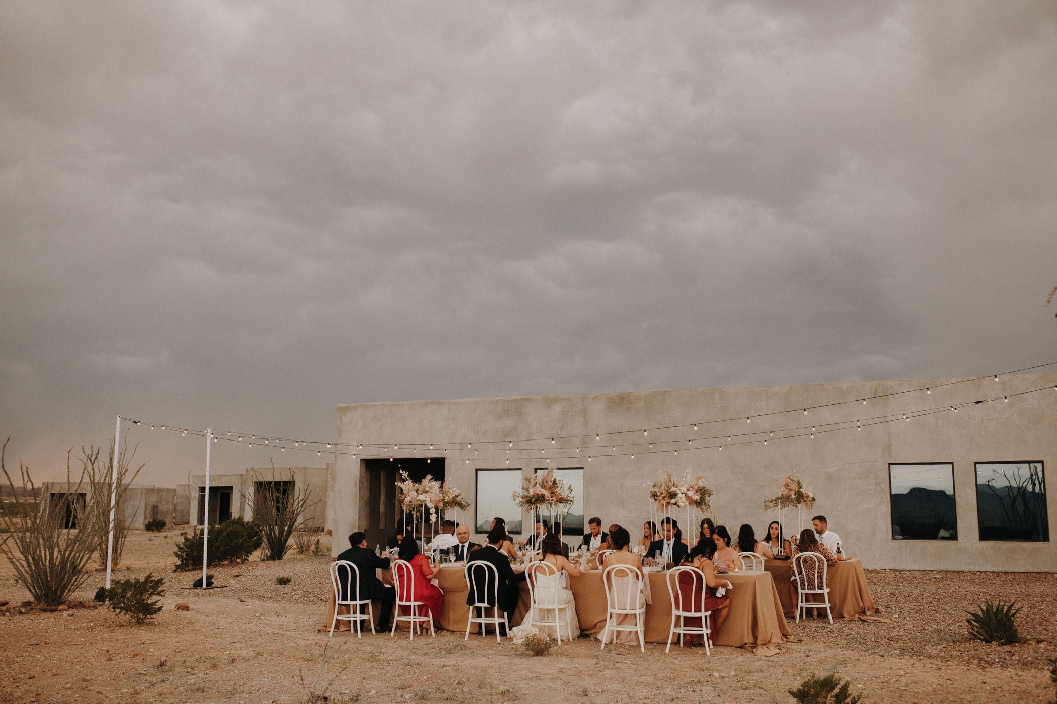 30 guests enjoying an outdoor wedding while a storm approaches
