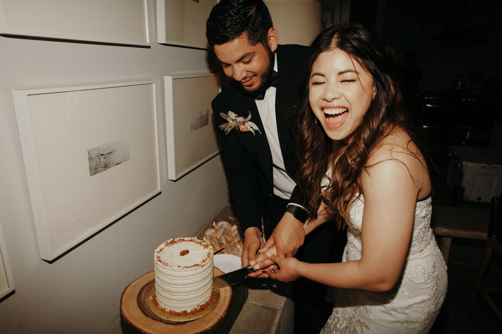 Bride and groom laughing while cutting their wedding cake