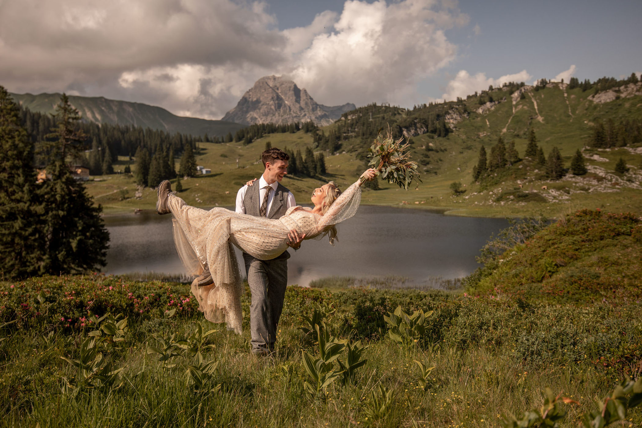 Groom carrying bride lovingly as she holds her bouquet in the air