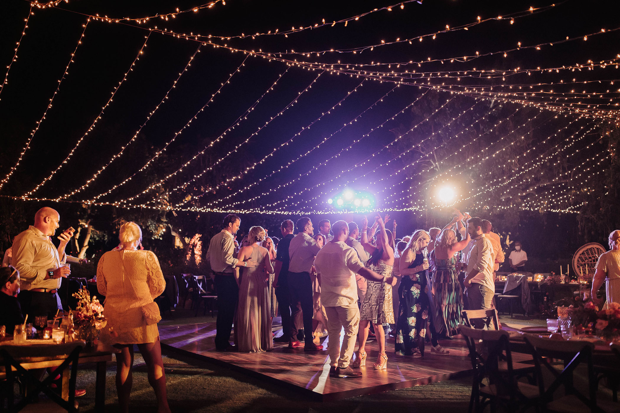 Guests partying at a wedding reception under twinkle lights at night