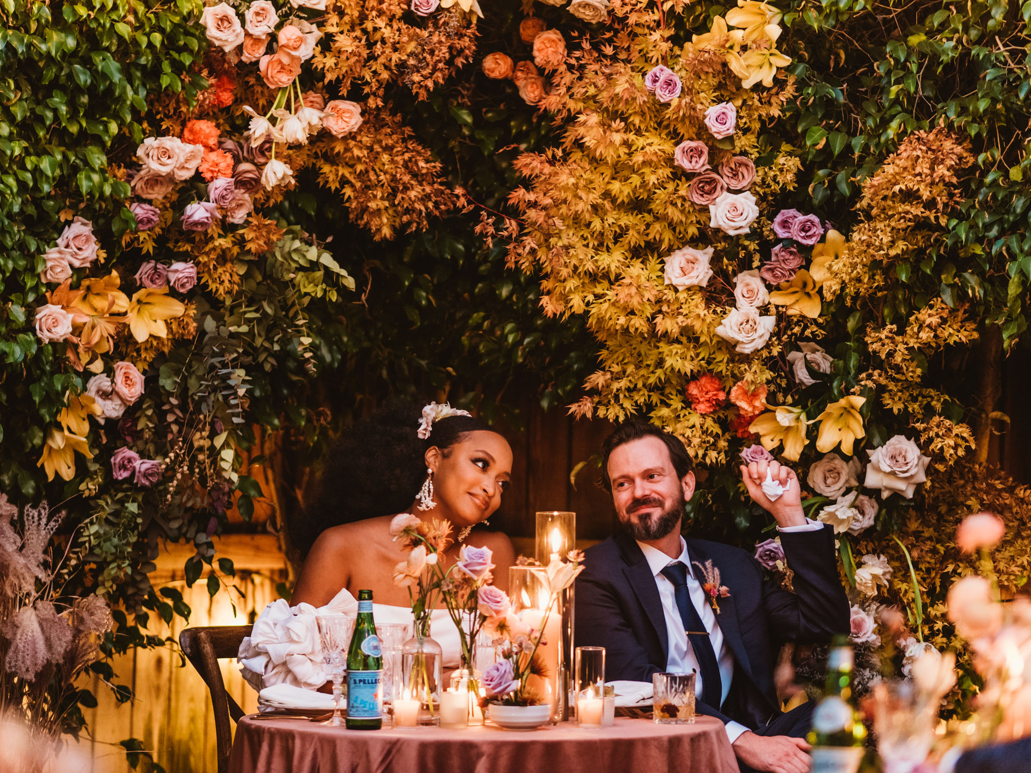Groom stares lovingly at his bride at their wedding dinner