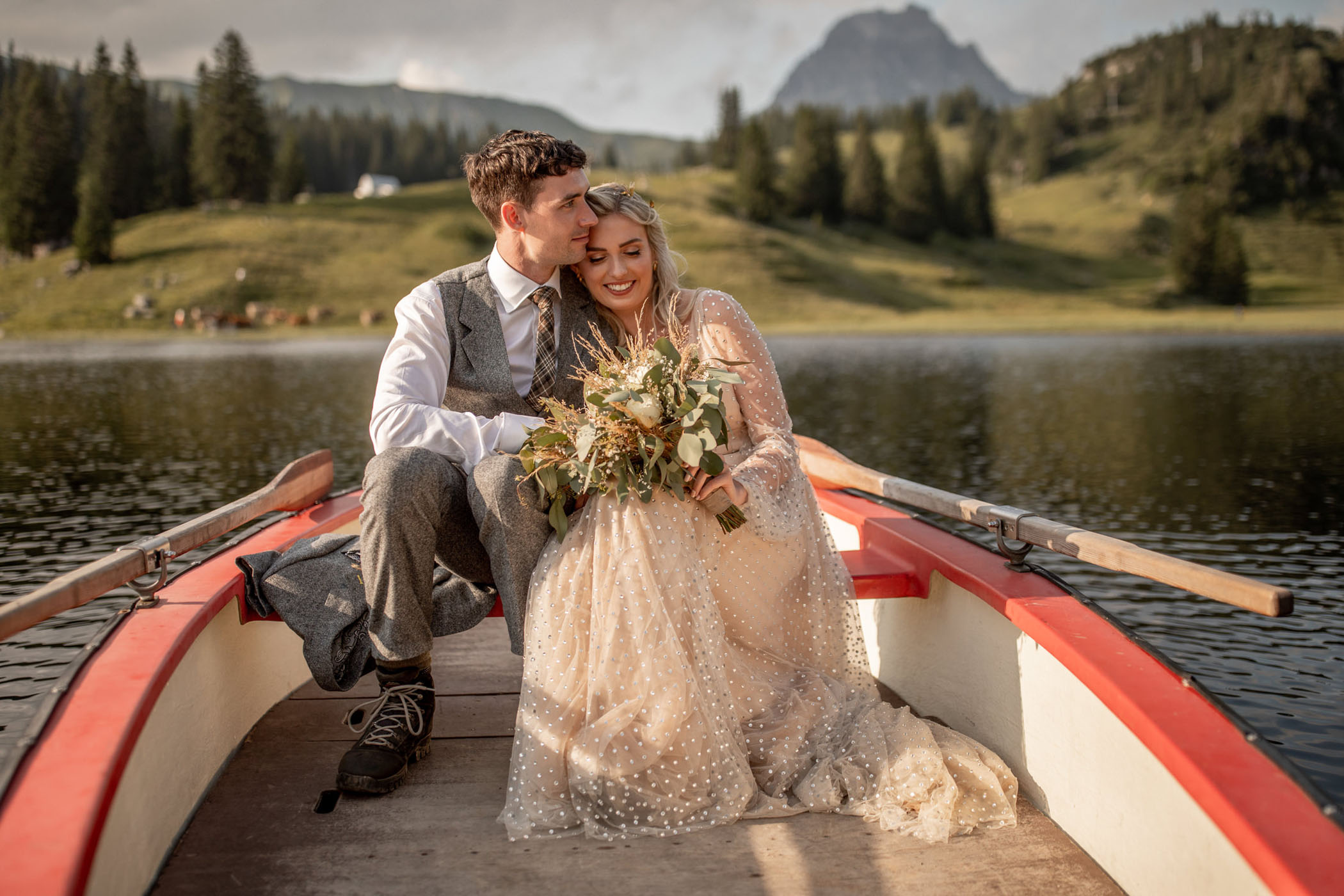 Just married couple snuggle on a canoe in the Austrian alps