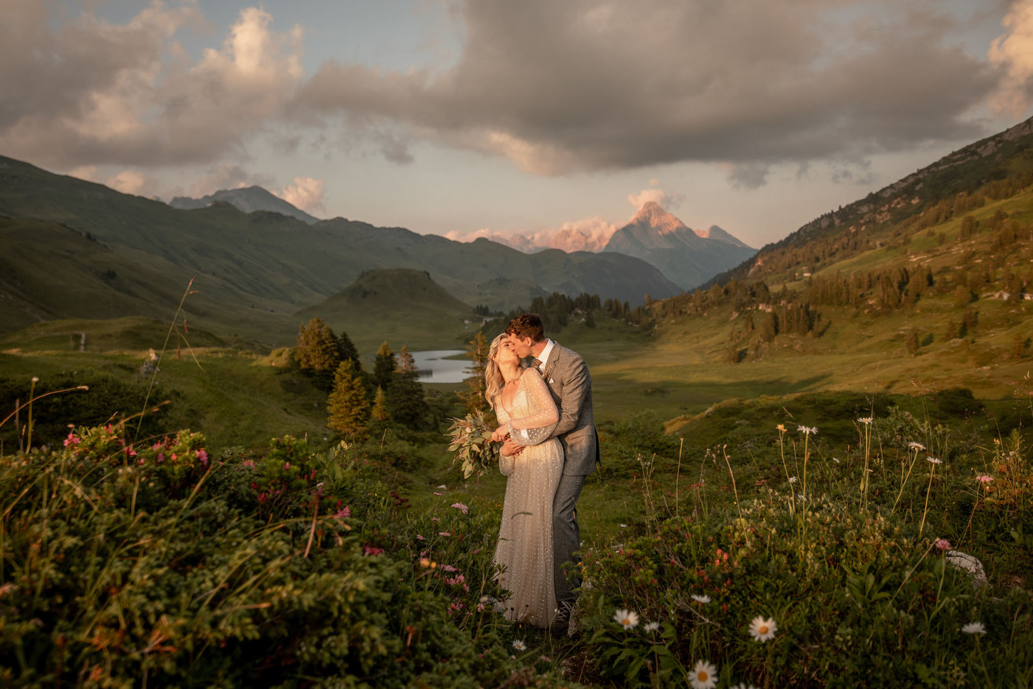 Husband and wife kissing in a wildlflower field